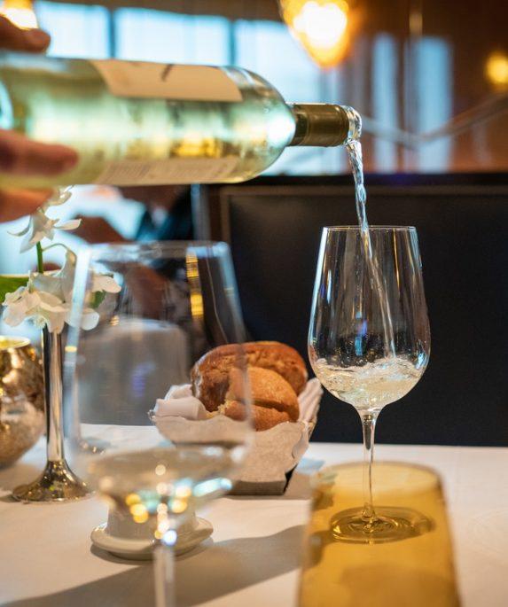 bouteille de pinot gris coulée sur verre à vin posé sur table de restaurant
